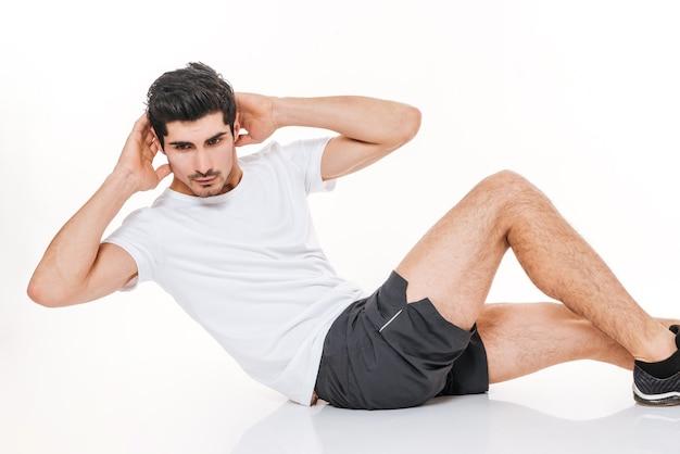 L'immagine di uno sportivo attraente in palestra fa esercizi sportivi sul pavimento sopra il muro bianco.