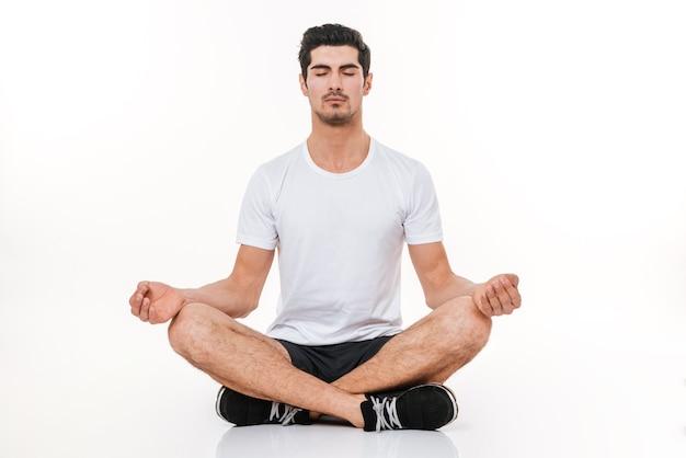 Immagine dello sportivo attraente in palestra che si siede sul pavimento sopra la parete bianca. occhi chiusi. concetto di yoga.