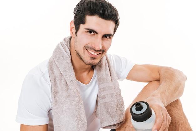 Immagine dello sportivo attraente con l'asciugamano in palestra che si siede sul pavimento sopra la parete bianca. sorridere tenendo una bottiglia d'acqua.