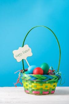 Immagine del cestino con le uova variopinte con desiderio di buona pasqua