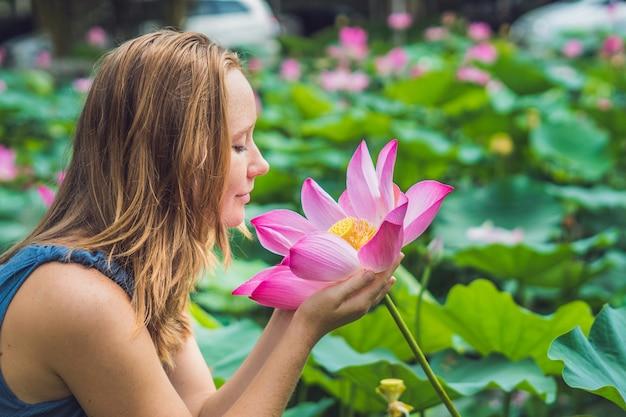 Immagine di bella donna dai capelli rossi con fiore di loto in mano