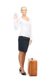 Foto di bella donna con valigia marrone