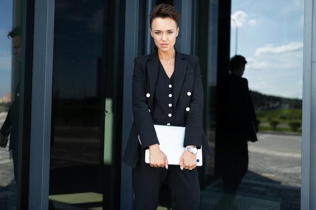 Foto di bella donna con i capelli scuri corti in abito da ufficio ha preso un appuntamento e sta aspettando un collega vicino al loro ufficio