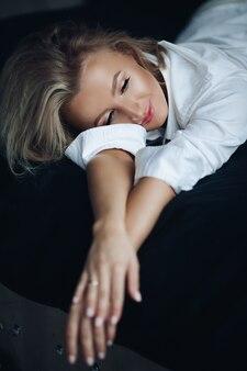 L'immagine di bella giovane femmina caucasica con capelli biondi lunghi in camicia bianca posa per la macchina fotografica
