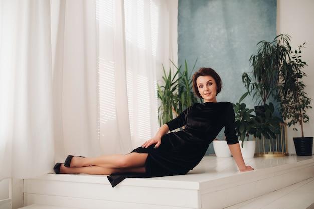 Immagine di una bellissima giovane donna caucasica con lunghi capelli biondi, bel viso, trucco luminoso, orecchini luminosi in un lungo abito nero