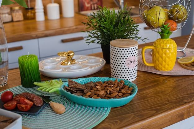 Immagine della grande cucina luminosa con armadi bianchi e marroni con bollitore per tè all'ananas giallo, macinapepe bianco e metallo appeso con frutta e biscotti