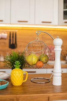 Immagine della grande cucina luminosa con armadi bianchi e marroni con bollitore per tè all'ananas giallo, macinapepe bianco e metallo appeso con frutta