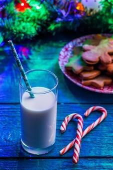 Immagine del tavolo blu con biscotti di natale, bicchiere di latte, bastoncini di caramello, rami di abete rosso con ghirlanda ardente
