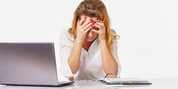 Immagine di una donna annoiata e stanca dietro il tavolo