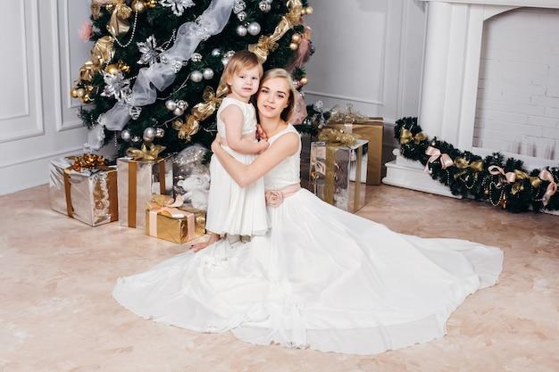 Immagine della famiglia caucasica di madre e figlia a capodanno con doni intorno all'albero di natale