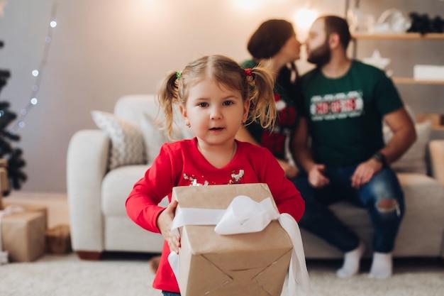 L'immagine della famiglia caucasica con una bambina graziosa festeggia il nuovo anno o il natale