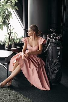 L'immagine di un'affascinante signora caucasica si siede sulla poltrona in pelle nera e posa per la fotocamera