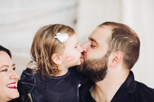 Immagine di una famiglia caucasica allegra con una bambina graziosa che festeggia il nuovo anno o il natale insieme...
