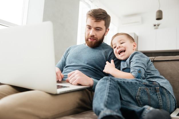 Immagine del padre allegro che utilizza il computer portatile con il suo piccolo figlio carino.
