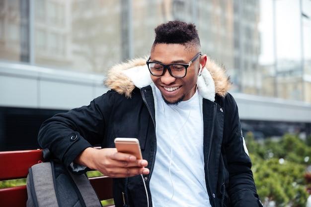 Immagine di un uomo allegro che tiene il cellulare in mano e chiacchiera mentre ascolta musica all'aperto.