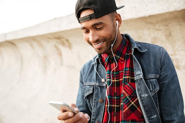 Immagine di un giovane allegro che indossa un berretto che cammina sulla spiaggia e chiacchiera con il telefono mentre ascolta musica con gli auricolari.