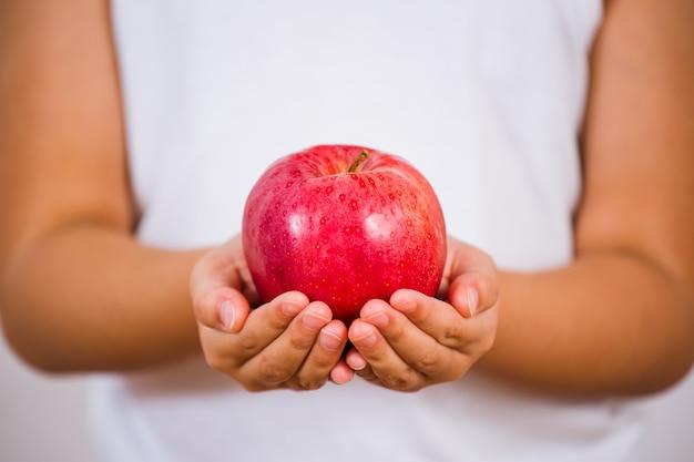 L'immagine di un bambino che tiene in mano una mela verde e rossa è sana e buona per un bianco.