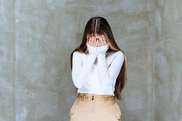 Foto di un modello di ragazza carina in piedi e chiudendo il viso con le mani