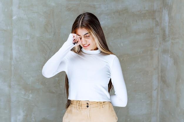 Foto di un modello di ragazza carina in piedi e in posa contro la pietra