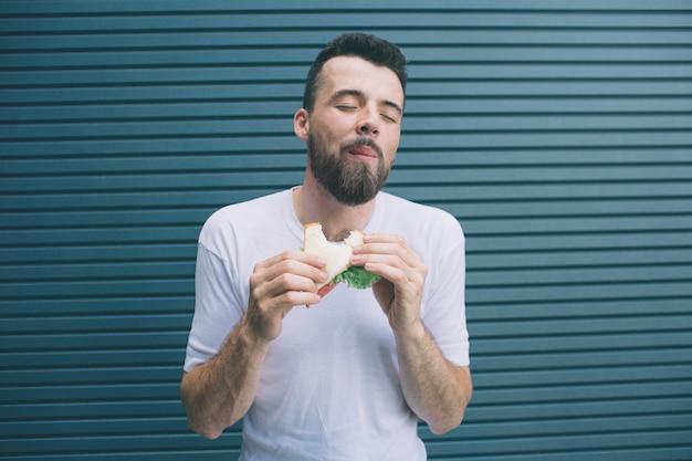 Un'immagine dell'uomo delizioso che gode del suo pasto. sta masticando un pezzo di sandwich e tenendo gli occhi chiusi. isolato su strisce