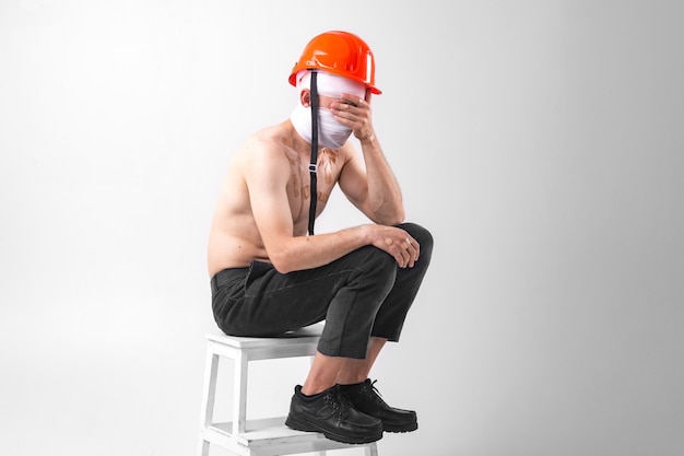 L'immagine dell'uomo disperato con la testa bendata si siede su una sedia con l'elmetto protettivo sulla sua testa e sul piangere