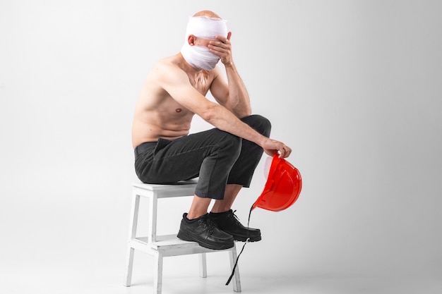 L'immagine dell'uomo disperato con la testa bendata si siede su una sedia con il casco protettivo