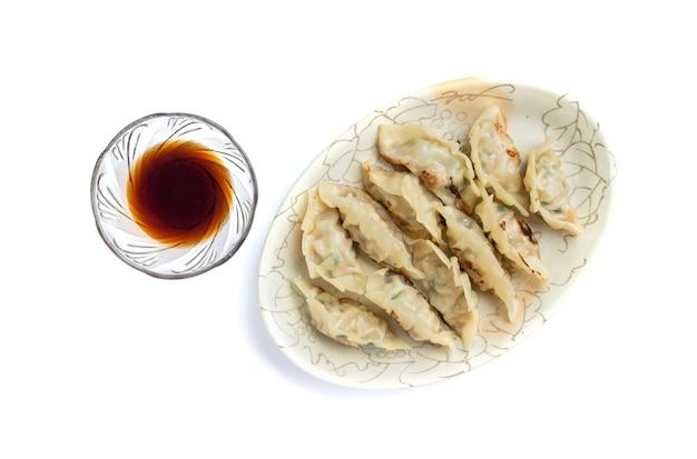 Foto di gnocchi o gyoza con salsa di soia isolati su sfondo bianco