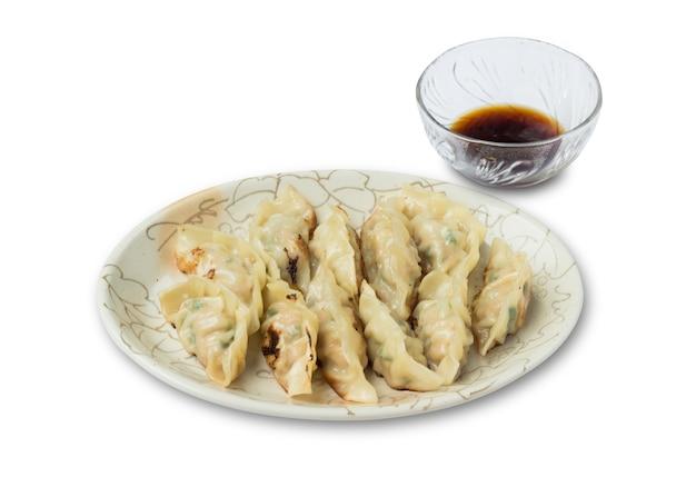 Immagine di gnocchi o gyoza con salsa di soia isolati su sfondo bianco