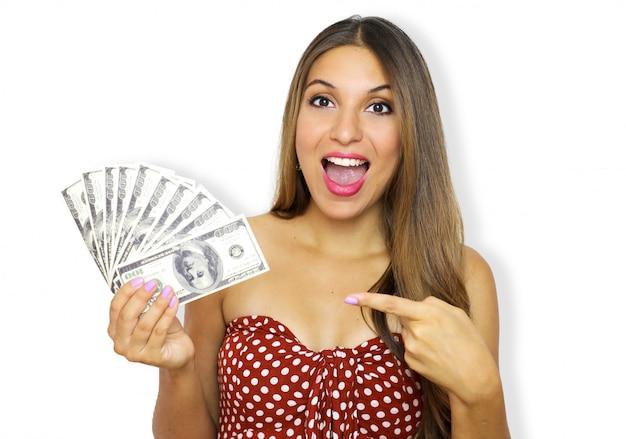 Foto di eccitata giovane donna allegra in piedi e indossando abiti senza spalline tenendo i soldi