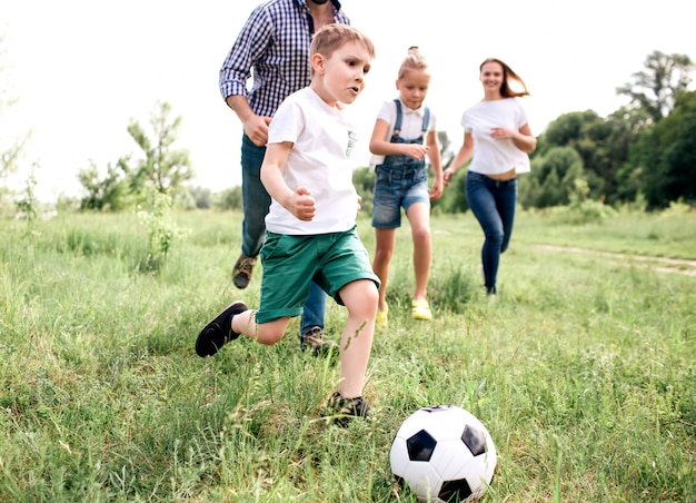 Un'immagine della famiglia che gioca a calcio insieme. il ragazzo corre di fronte a tutti. c'è un uomo che corre dietro di lui e anche delle ragazze. stanno giocando sul prato.