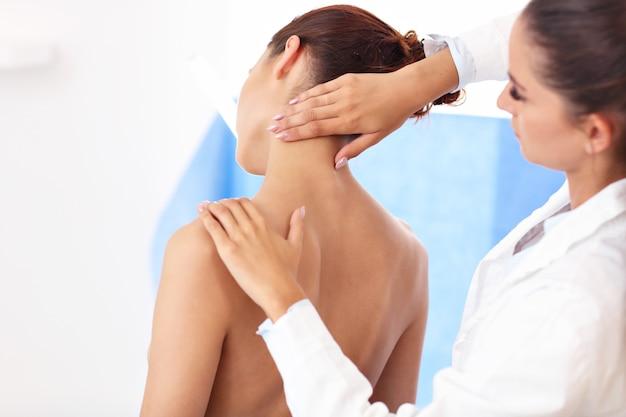 Immagine di una fisioterapista che aiuta un paziente con problemi alla schiena in clinica