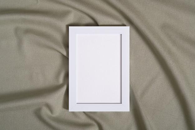 Cornice con mockup di carta di carta bianca su tessuto di colore neutro verde