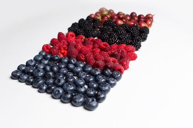 Immagine di frutti di bosco freschi situati in linea, sul tavolo bianco.
