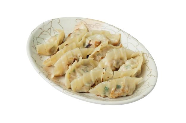 Immagine di gnocchi fritti o gyoza in un piatto isolato su sfondo bianco