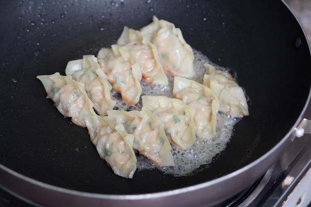 Immagine di gnocchi fritti gyozas con carne di maiale cotta in padella