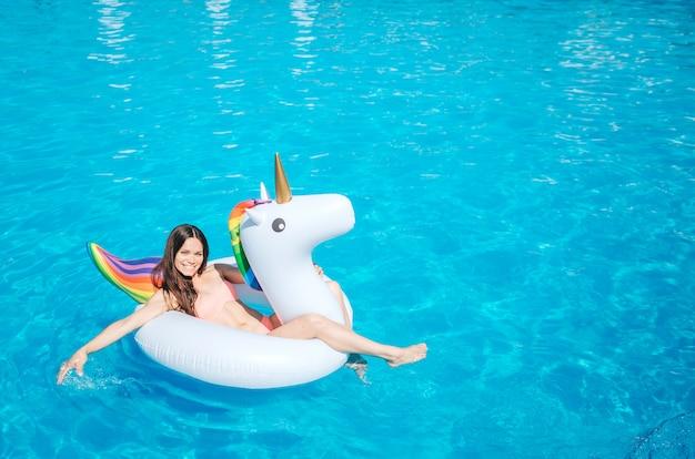 Un'immagine della ragazza che si trova sul materasso di aria e sull'acqua commovente nella piscina con la sua mano. lei si diverte molto. la ragazza guarda in basso.