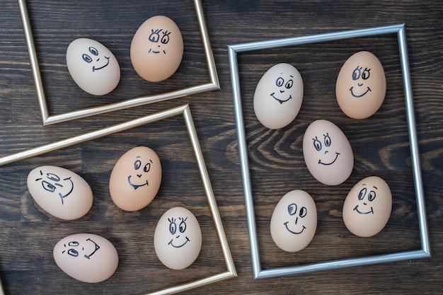 Cornice dorata dell'immagine e molte uova divertenti che sorridono sul fondo di legno scuro della parete, fine su. ritratto del fronte di emozione della famiglia delle uova. concetto di cibo divertente