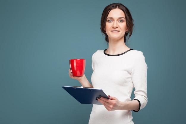 Foto di bella donna in abiti leggeri in piedi con caffè e registrazioni nelle mani