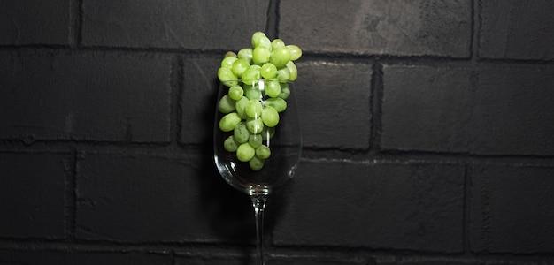 Immagine dell'uva verde nel bicchiere di vino, isolata sul muro di mattoni nero.