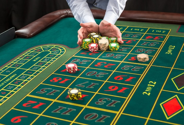 Immagine di un tavolo verde e scommesse con fiches. l'uomo consegna le fiches del casinò sul tavolo della roulette. avvicinamento