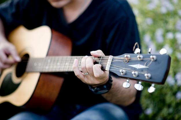Immagine di un chitarrista, un giovane che gioca una chitarra mentre sedendosi in un giardino naturale, concetto di musica