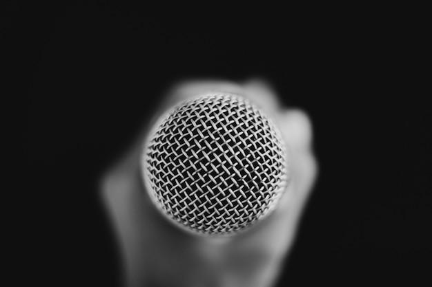 Immagine di una mano che tiene un microfono sul nero