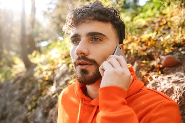 Foto di bello serio giovane sportivo fitness uomo corridore all'aperto nel parco parlando dal telefono cellulare.