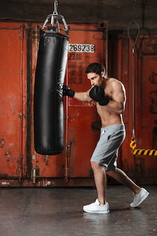 Immagine di un bel giovane pugile che si allena in una palestra con sacco da boxe.