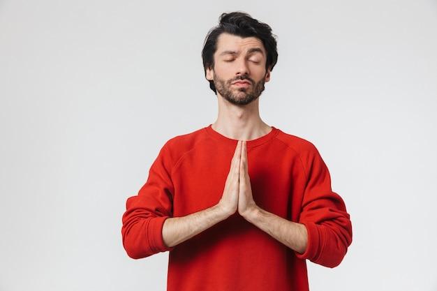 L'immagine di un bel giovane uomo concentrato in posa sopra il muro bianco medita.
