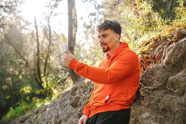 Foto di corridore uomo fitness sport giovane bello all'aperto nel parco ascoltando musica con gli auricolari utilizzando il telefono cellulare prendere un selfie parlando.