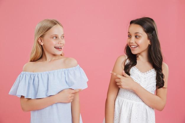 Immagine di felice bruna e ragazze bionde di 8-10 anni che indossano abiti sorridenti e puntando il dito a vicenda.