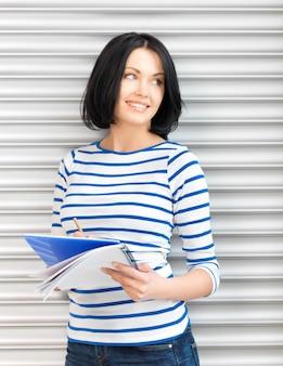 Foto di un'adolescente felice e sorridente con un grande blocco note