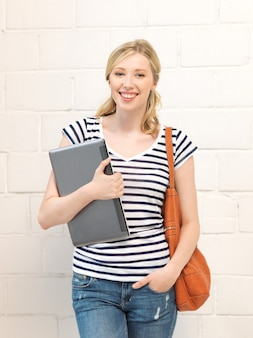 Foto di un'adolescente felice e sorridente con un laptop