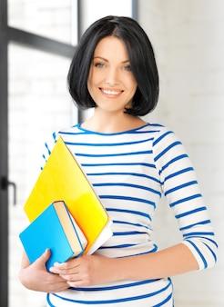 Foto di un'adolescente felice con libri e cartelle